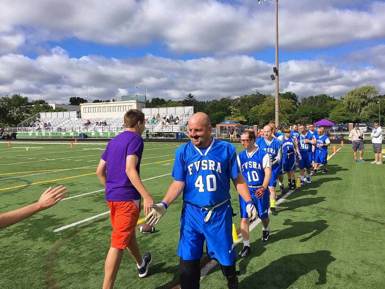 Members of the Fox Valley Special Recreation Association, including Douglas Burson (40) and David Colby (10), shake hands with opponents from the DuPage Valley Special Athletes during the Special Olympics of Illinois flag football tournament Sunday at Stevenson High School in Lincolnshire.