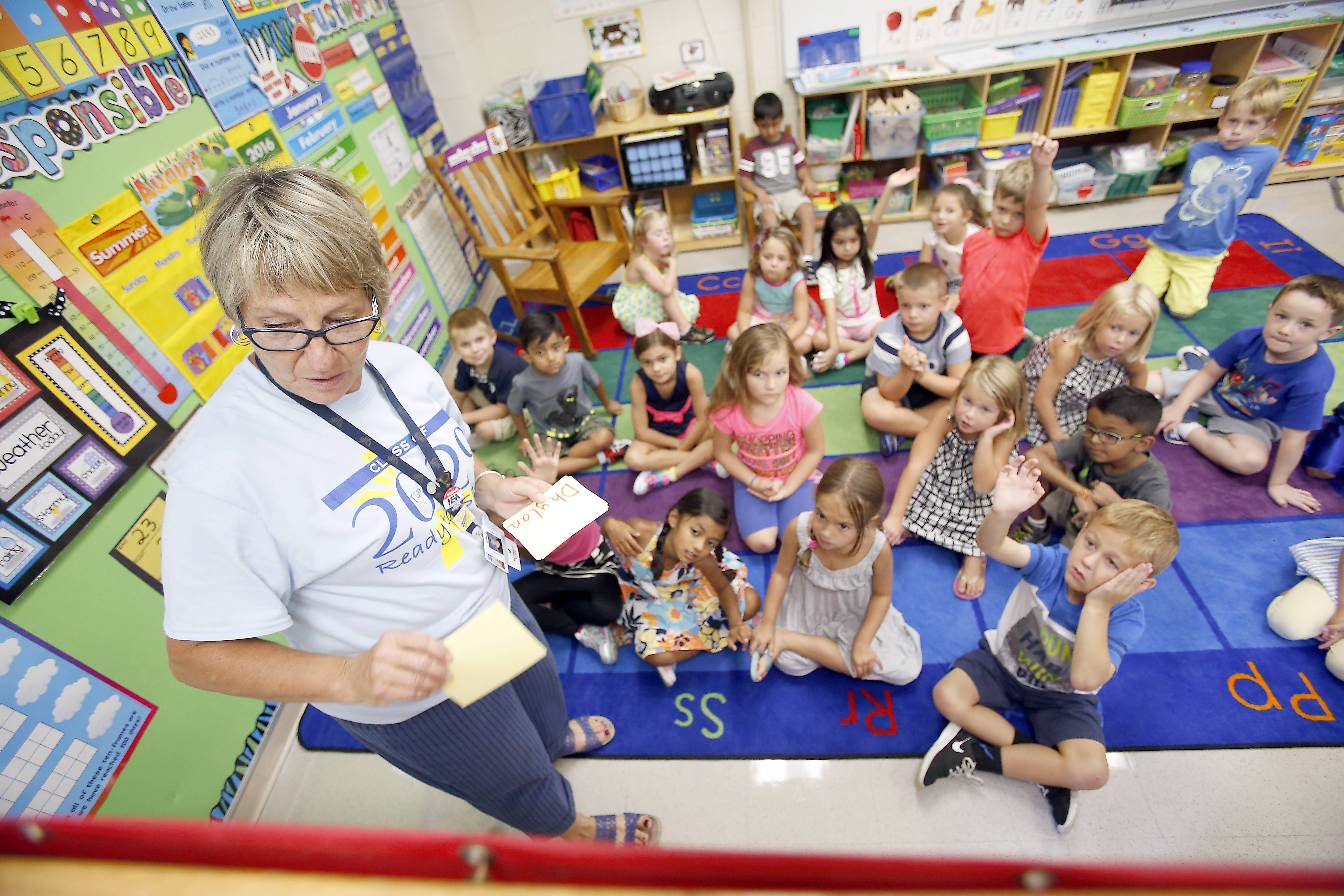 Kindergarten teacher Jan Wilcox tends to her young charges during the first day of full-day kindergarten at Centennial School in Bartlett.