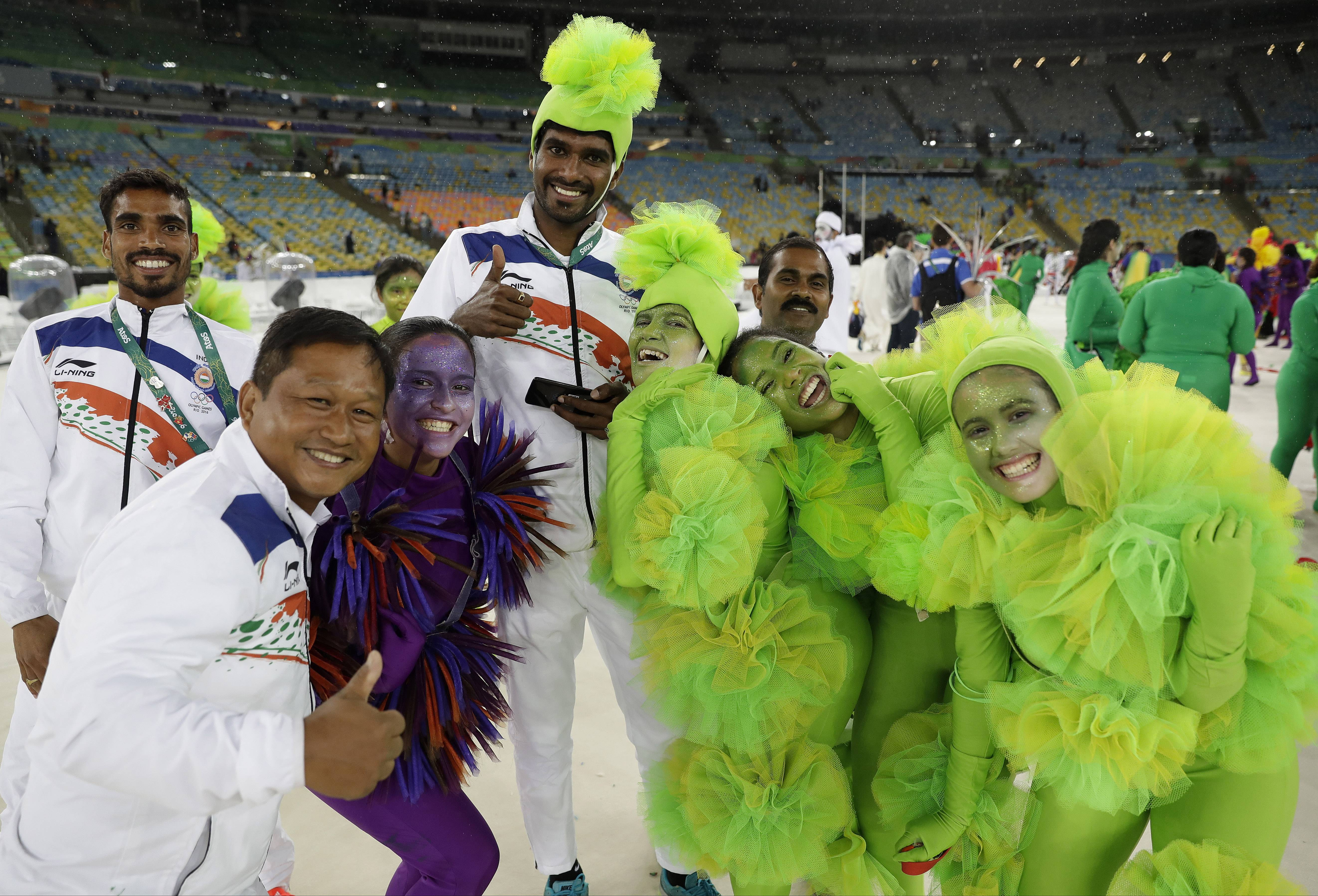Athletes pose for picture with performers during the closing ceremony in the Maracana stadium at the 2016 Summer Olympics in Rio de Janeiro, Brazil, Sunday, Aug. 21, 2016. (AP Photo/Matt Dunham)