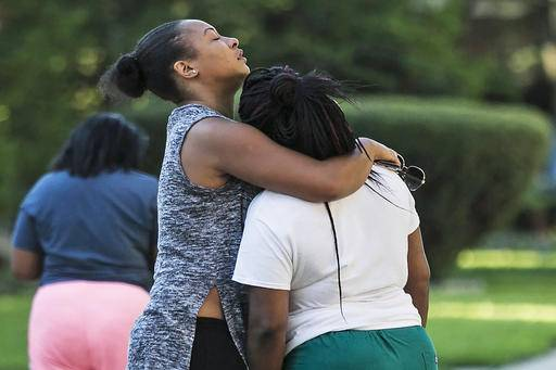 Mourners console each other near the scene where an apartment building fire in Chicago early Tuesday, Aug. 23, 2016, killed several people. Police said the fire appears to have been deliberately set. (Ashlee Rezin/Chicago Sun-Times via AP)
