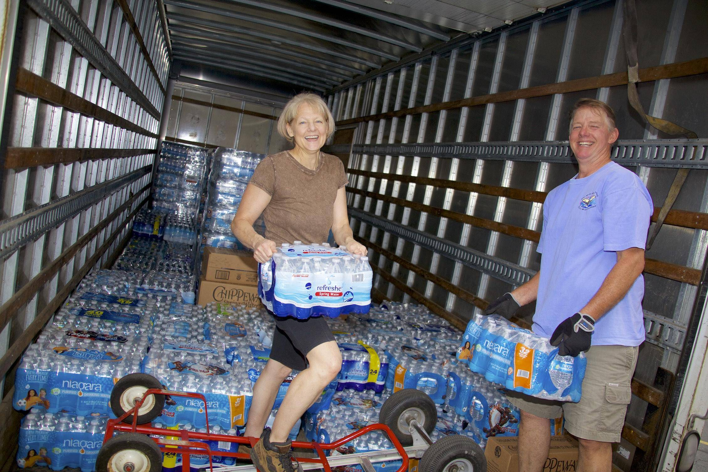 Volunteer drivers Heidi and Scott Heifetz load bottled water into a truck at Bethlehem Lutheran Church in West Dundee.