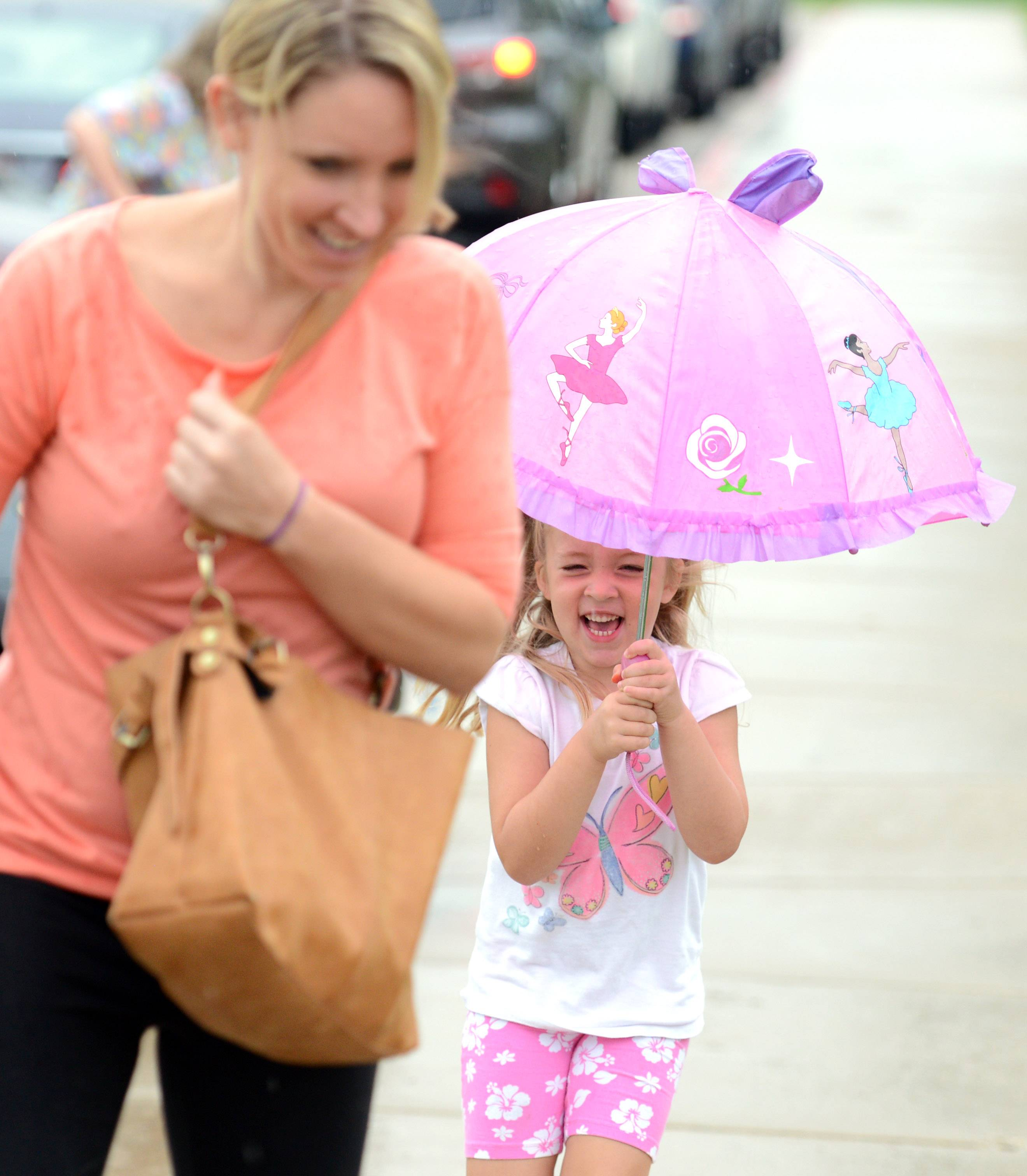 Incoming kindergartner Makenna Donaldson and her mom Mandy hurry up the sidewalk Wednesday as the rain falls before the first day of classes for Burlington Central Unit District 301 at Prairie View Grade School in Elgin.