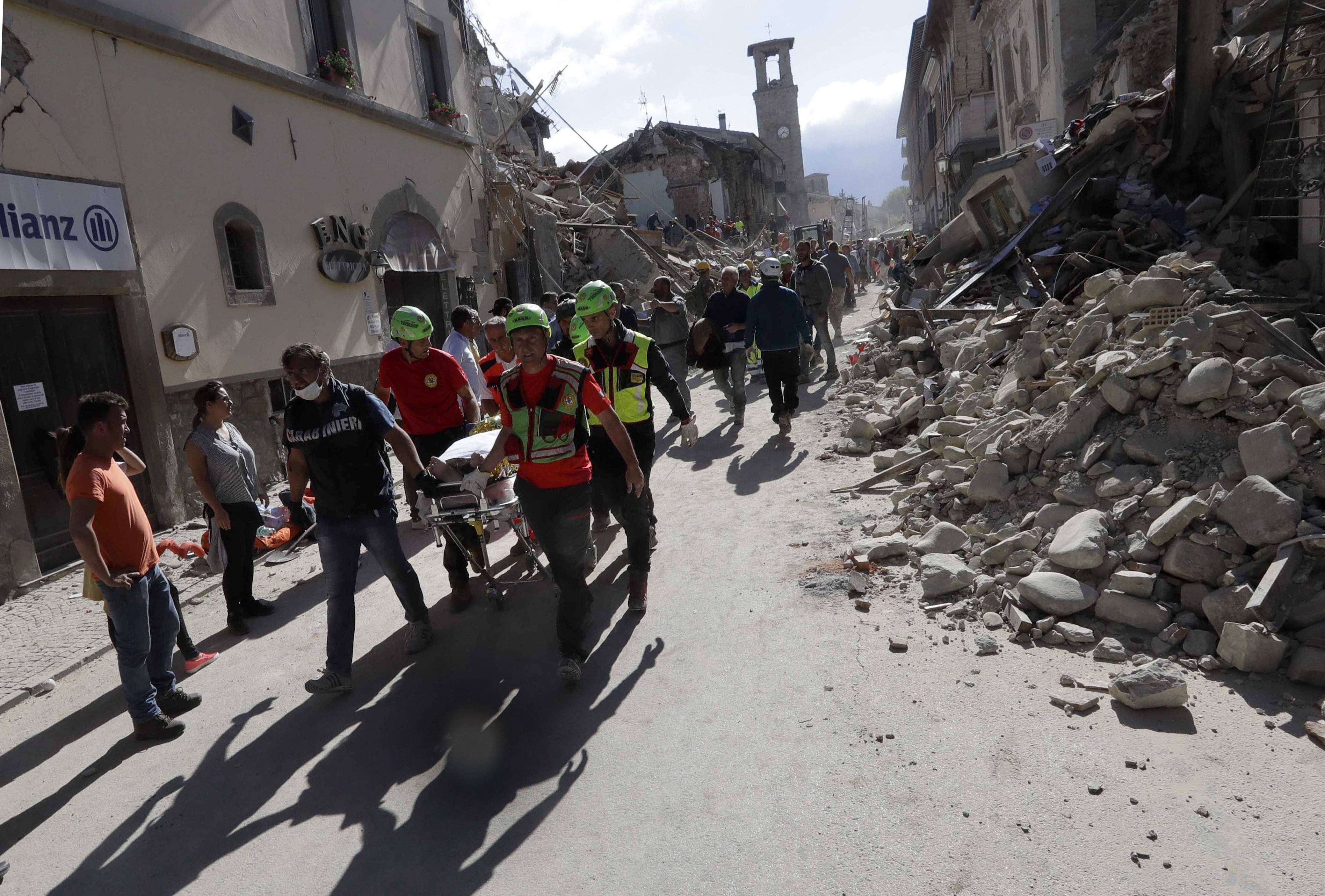 The body of a victim is pulled out of the rubble following an earthquake in Amatrice Italy, Wednesday, Aug. 24, 2016. The magnitude 6 quake struck at 3:36 a.m. (0136 GMT) and was felt across a broad swath of central Italy, including Rome where residents of the capital felt a long swaying followed by aftershocks. . (AP Photo/Alessandra Tarantino)