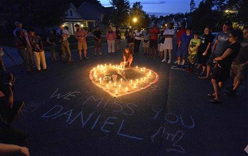 Friends and family of Daniel Harris gather around a heart drawn onto Seven Oaks Drive during a candlelight vigil to remember Harris, a deaf motorist who was shot and killed by a state trooper, Monday, Aug. 22, 2016 in Charlotte, N.C. Harris, a deaf man who was shot and killed by a North Carolina state trooper after he didn't stop for the officer's blue lights was unarmed and likely did not understand the officer's commands, the slain man's family says. (David T. Foster III/The Charlotte Observer via AP)