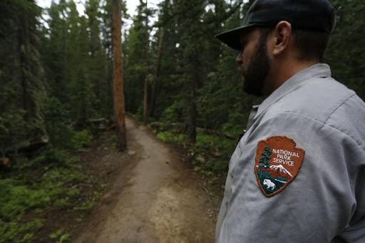 Park Service employee Jesse Miller pauses while working to repair a trail  destroyed in a major c960110062fe