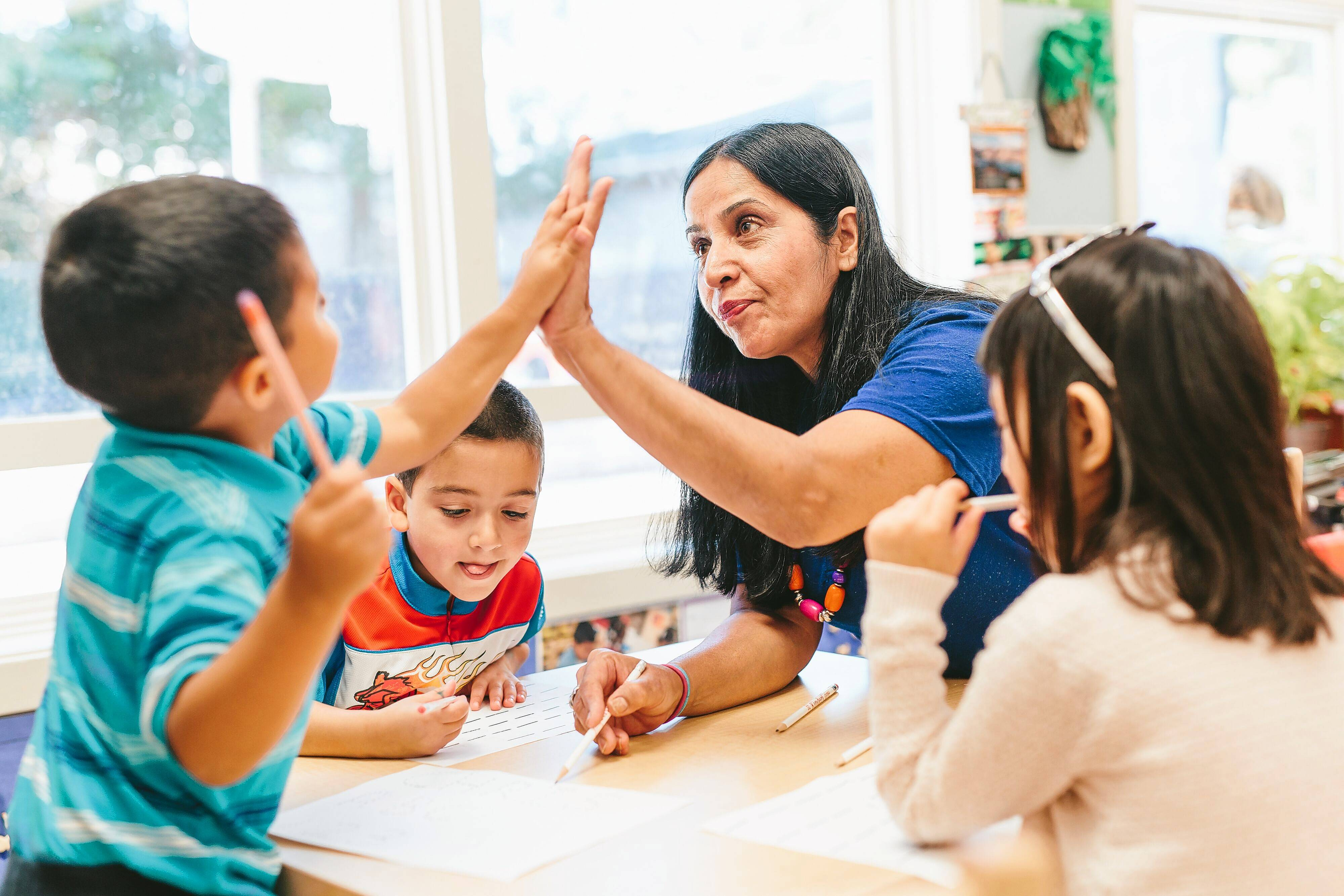 Attiya Mirza high-fives one of her students at Quentin Park KinderCare in Palatine Monday just before she was surprised with a $10,000 award for her excellence in teaching.