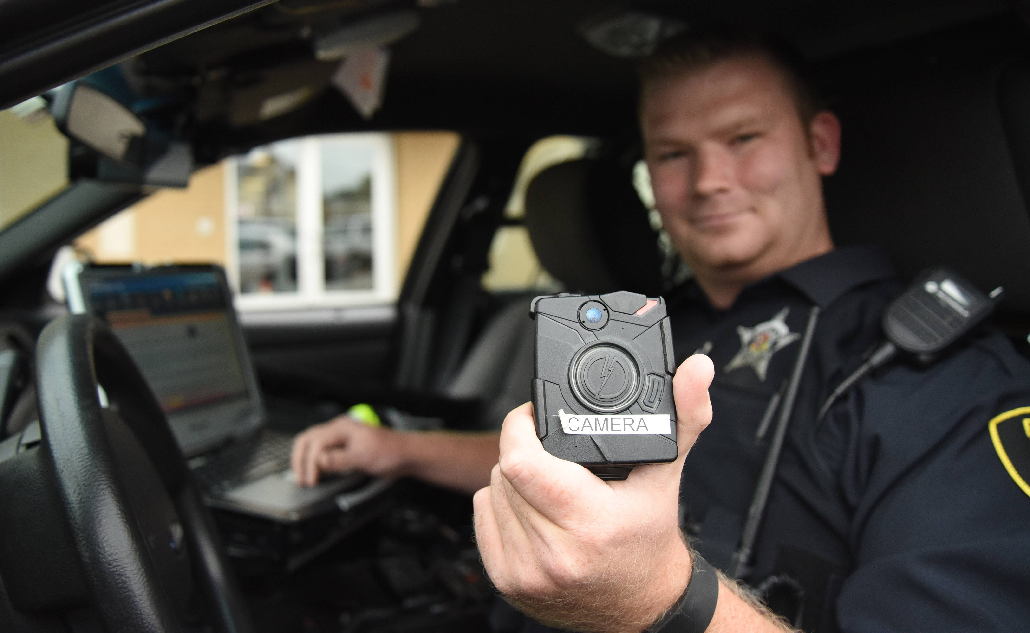Elgin has put out a request for bids for 200 body cameras for police officers. Here, officer Michael Hutton shows a Taser Axon Body camera that he tested as part of a pilot program that ended in June.