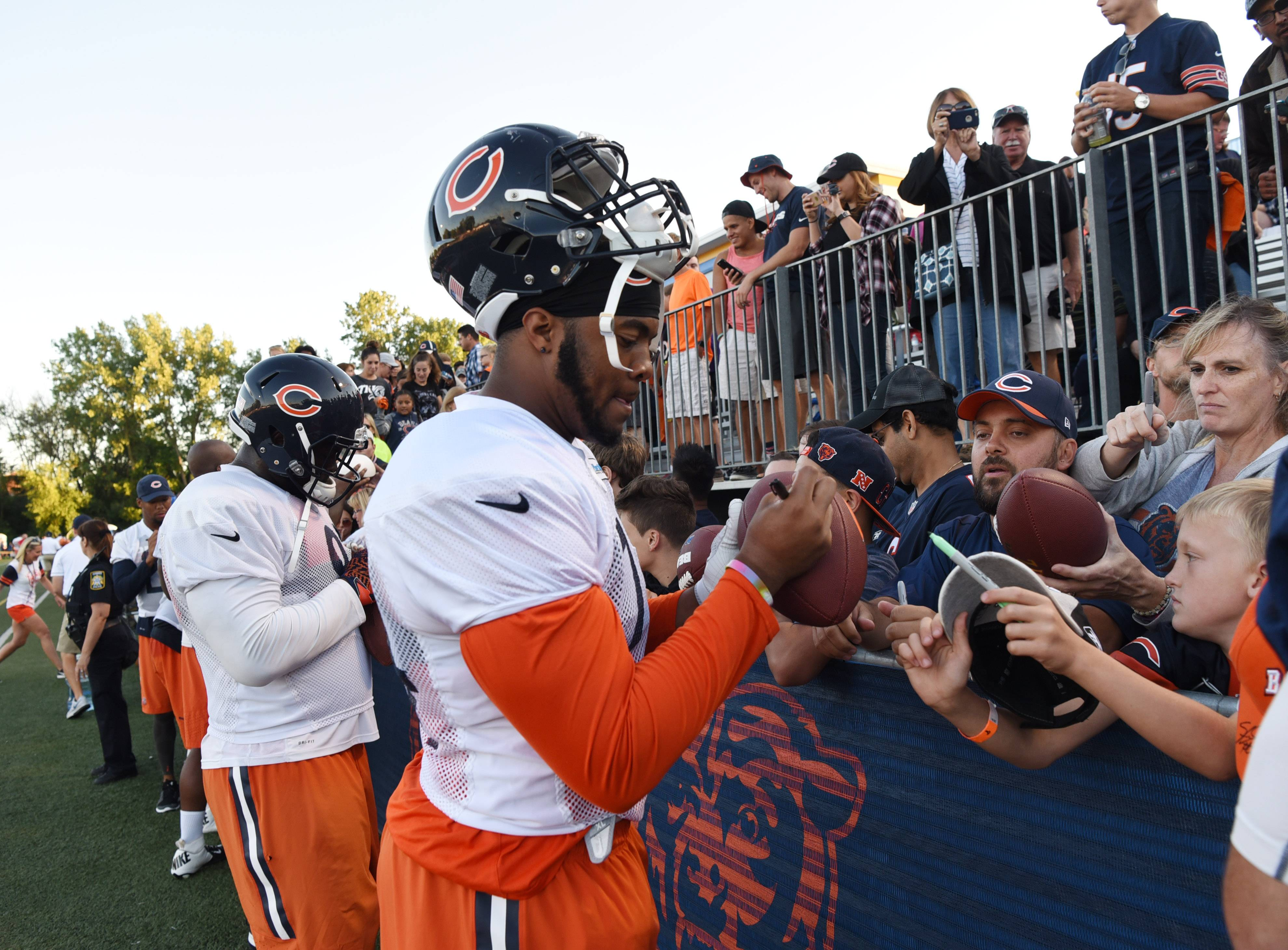 Defensive lineman Jonathan Bullard and teammates sign autographs for fans following a recent Chicago Bears practice at Warren High School in Gurnee.