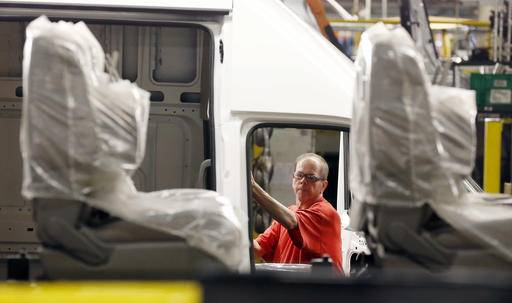 In this April 6, 2016, photograph, front seats await placement in a vehicle while a technician works on the door frame of an NV Cargo Van in the background, at the Nissan Canton Vehicle Assembly Plant in Canton, Miss. On Thursday, Aug. 25, 2016, the Commerce Department releases its July report on durable goods. (AP Photo/Rogelio V. Solis)