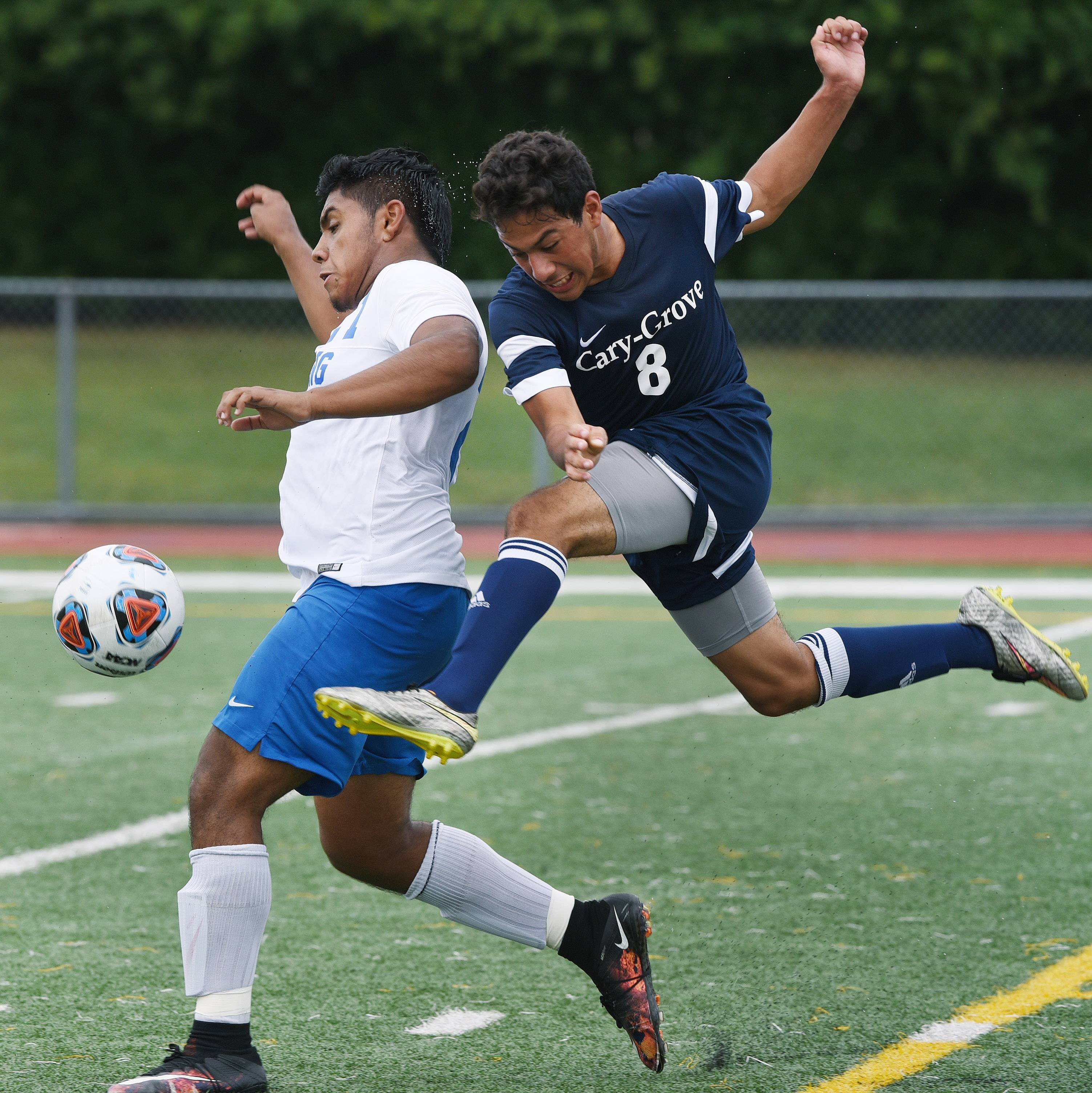 Cary-Grove's Jesus Angeles, right, goes airborne as he pursues the ball alongside Wheeling's Rivaldi Araujo during Saturday's soccer game at Wheeling.