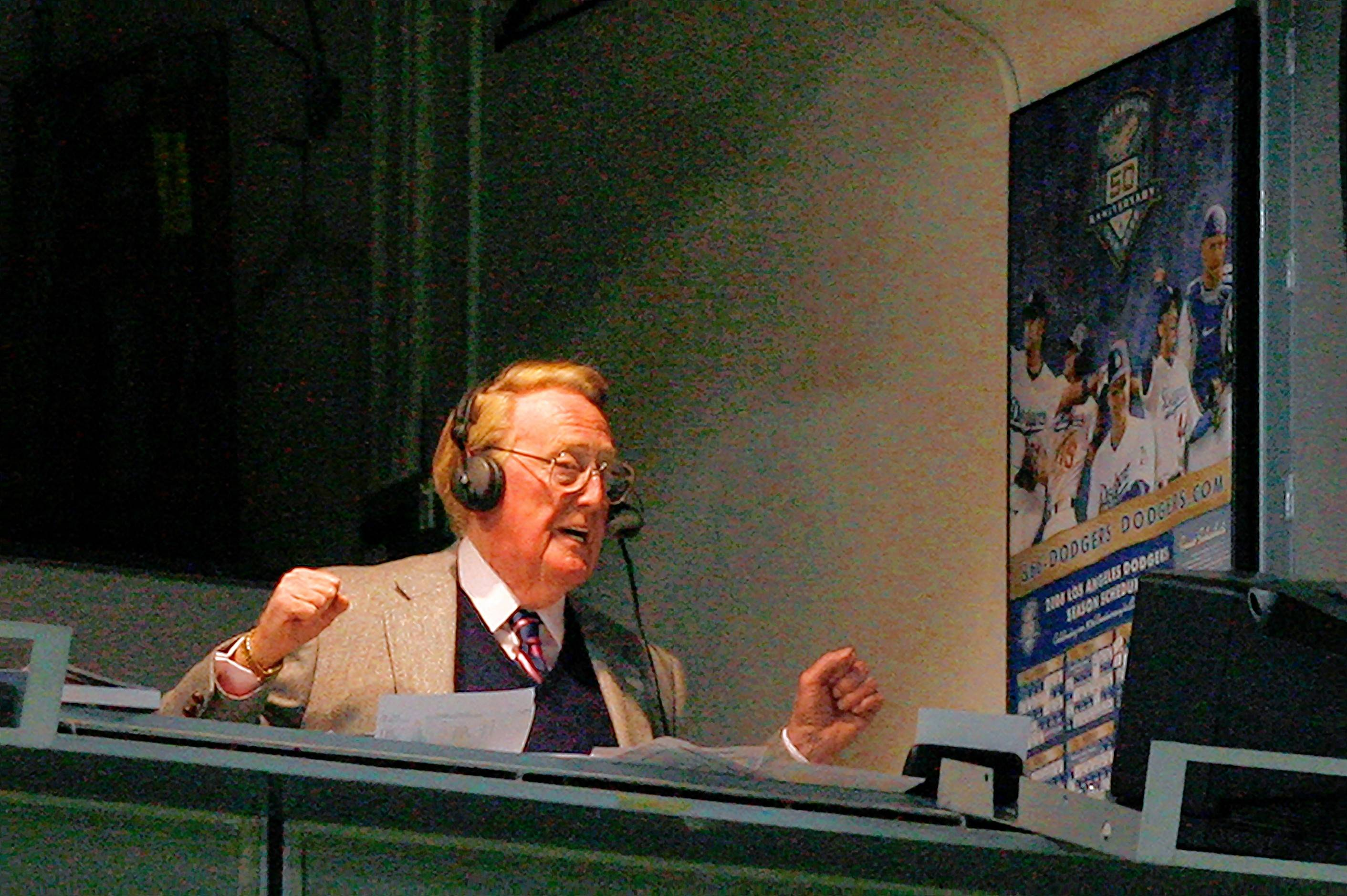 Sportscaster Vin Scully broadcasts from the booth at Dodger Stadium in Los Angeles. He's retiring at the end of this season after 67 years.