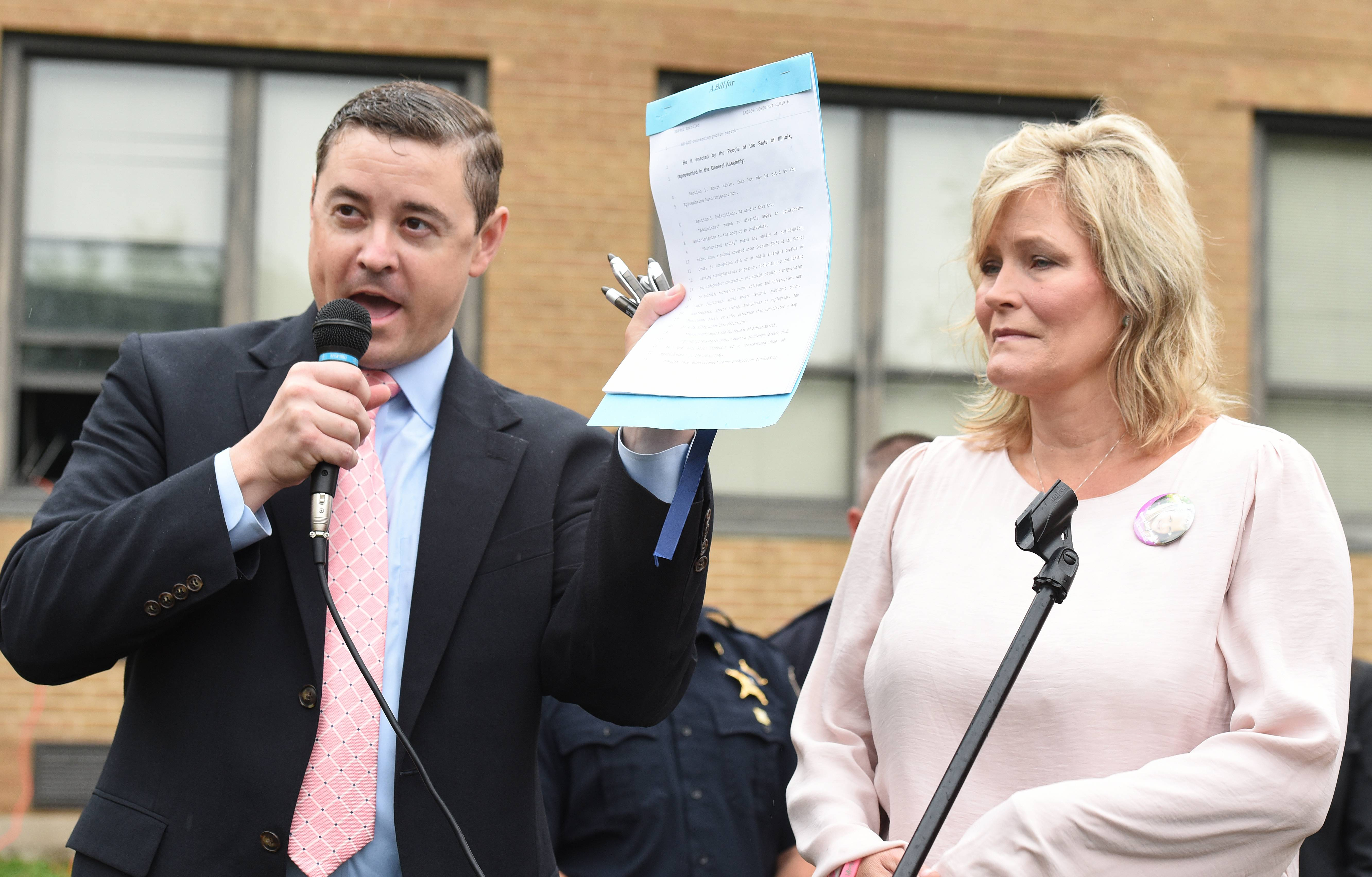 Republican state Sen. Chris Nybo of Elmhurst and Shelly LeGere show off a copy of the Annie LeGere Law that authorizes police to carry and administer epinephrine auto-injectors at Sandburg Middle School in Elmhurst Saturday.