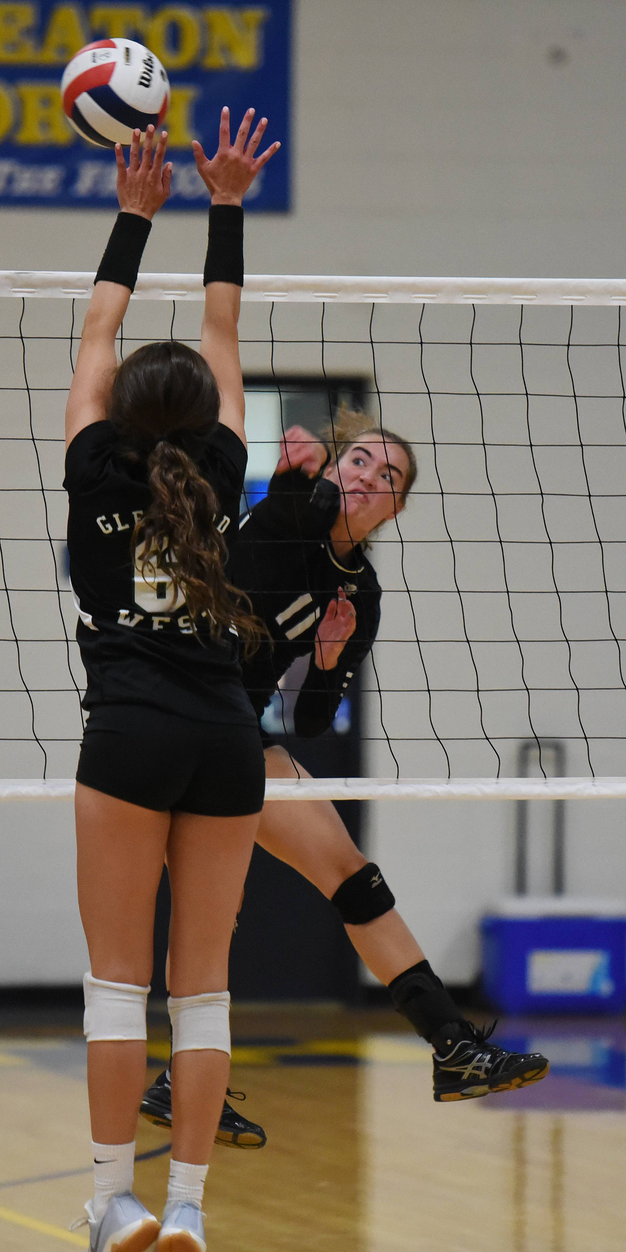 Paul Michna/pmichna@dailyherald.comHannah Brodner of Glenbard West attempts to block a shot from Jessica Weber of Kaneland during game acton Saturday at Wheaton North.