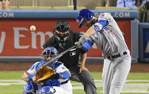 Chicago Cubs' Kris Bryant hits a two-run home run as Los Angeles Dodgers catcher Carlos Ruiz, left, watches along with home plate umpire Alfonso Marquez during the 10th inning of a baseball game, Friday, Aug. 26, 2016, in Los Angeles. (AP Photo/Mark J. Terrill)