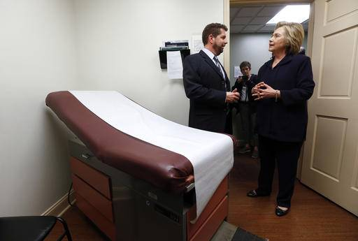 FILE - In this May 2, 2016 file photo, Democratic presidential candidate Hillary Clinton listens to Dr. Christopher Beckett, CEO of Williamson Health and Wellness Center during a tour an exam room of the facility in Williamson, W.Va. With the hourglass running out for his administration, President Barack Obama�€™s health care law is struggling in many parts of the country. Double-digit premium increases and exits by big-name insurers have caused some to wonder whether �€œObamacare�€� will go down as a failed experiment. (AP Photo/Paul Sancya)