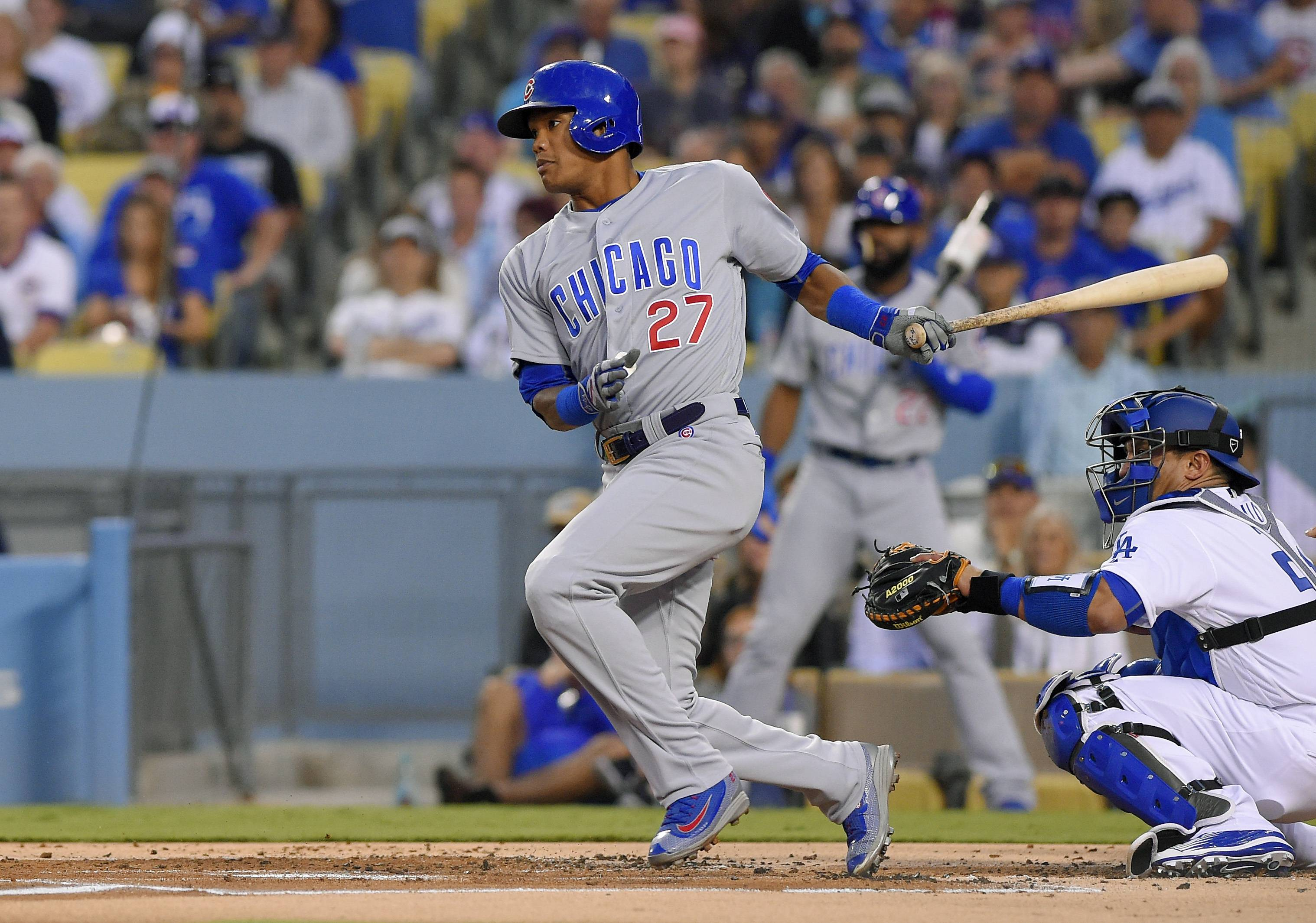 Chicago Cubs' Addison Russell, left, hits an RBI-single as Los Angeles Dodgers catcher Carlos Ruiz watches during the first inning of a baseball game, Friday, Aug. 26, 2016, in Los Angeles. (AP Photo/Mark J. Terrill)
