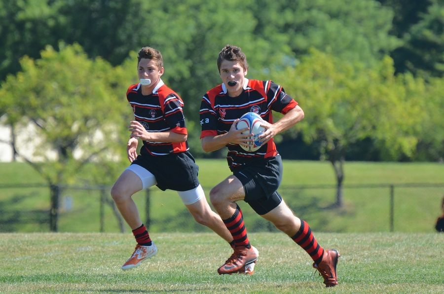 Vince Carso of Hersey High School, left, and Matt Conley of Buffalo Grove High School coordinate their attack at July's State Olympic Rugby Championship at Melas Park in Mount Prospect.