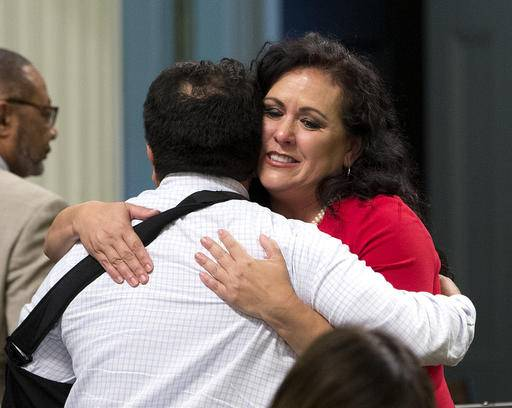 Assemblywoman Lorena Gonzalez, D-San Diego, receives congratulations from Assemblyman Jimmy Gomez, D-Los Angeles after the Assembly approved her bill requiring farmworkers to receive overtime pay after working eight hours, at the Capitol, Monday, Aug. 29, 2016, in Sacramento, Calif. The measure, AB1066, now goes to the governor. (AP Photo/Rich Pedroncelli)