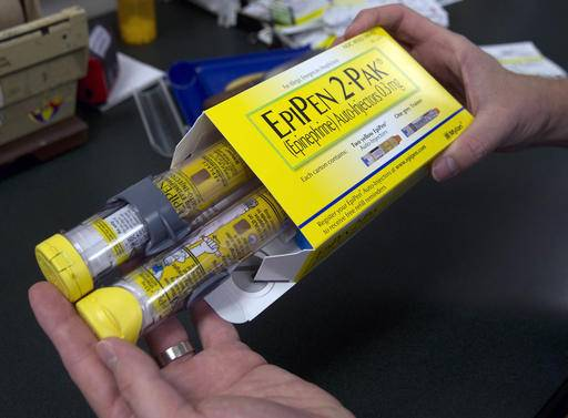 FILE - In this July 8, 2016, file photo, a pharmacist holds a package of EpiPens epinephrine auto-injector, a Mylan product, in Sacramento, Calif. Mylan said it will make available a generic version of its EpiPen, as criticism mounts over the price of its injectable medicine. (AP Photo/Rich Pedroncelli, File)