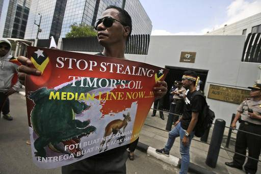 FILE - In this March 24, 2016 file photo, a protester holds a poster during a rally outside the Australian Embassy in Jakarta, Indonesia as dozens of people show their support to East Timor in the dispute over oil and gas revenue-sharing between the two countries. East Timor and Australia opened conciliation talks Monday, Aug. 29 in their bitter legal battle to set a permanent maritime boundary that will carve up billions of dollars in oil and gas reserves underneath the seabed. (AP Photo/Dita Alangkara, File)
