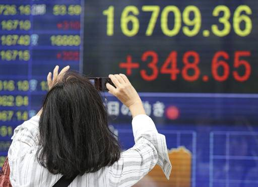 A woman takes a picture of an electronic stock board of a securities firm in Tokyo, Monday, Aug. 29, 2016. Most Asian stocks slipped Monday on remarks from the U.S. Federal Reserve late last week that the case has strengthened for raising interest rates, but the Tokyo market was an exception and gained on prospects for a strong dollar. (AP Photo/Koji Sasahara)