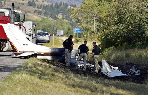 "Missoula County sheriff's deputies look at the wreckage of a Cessna 182 that crashed on the shoulder of Interstate 90 near Rock Creekont., on Sunday, Aug. 28, 2016. The crash killed 52-year-old Darrell Ward of Deer Lodge, a star of the History channel series ""Ice Road Truckers"" and pilot Mark Melotz, 56, of Arlee. Ward was returning to Montana to film a pilot episode of a documentary-type series about the recovery of plane wrecks. (Tom Bauer/The Missoulian via AP)"
