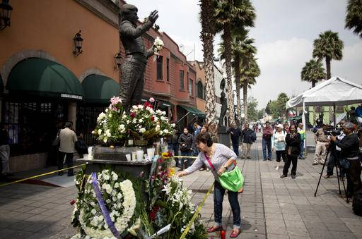A statue depicting superstar Mexican songwriter and singer Juan Gabriel has become a makeshift memorial where mourners are placing flowers and candles, in Mexico City's Garibaldi plaza, Monday, Aug. 29, 2016. Gabriel, who was an icon in the Latin music world, died Sunday at his home in California at age 66, his publicist said. He was born Alberto Aguilera Valadez and wrote his first song at age 13. (AP Photo/Eduardo Verdugo)