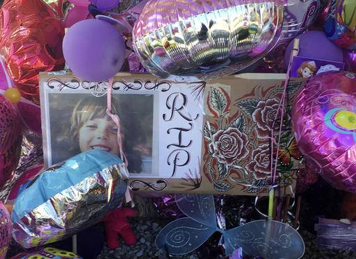A picture of Victoria Martens, a 10-year-old Albuquerque girl brutally murdered last week, is placed in a memorial outside her former Albuquerque apartment on Monday, Aug. 29, 2016. Stricken with grief, the grandparents and other family members of Martens, who was brutally slain last week, clutched one another and wept Monday as they made their first public comments and thanked the community for its outpouring of love and support. (AP Photo/Russell Contreras)