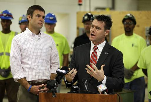 Republican U.S. Senate candidate Todd Young speaks after receiving the endorsement of the U.S. Chamber of Commerce in Indianapolis, Monday, Aug. 29, 2016. Indiana's Senate campaign has gained national prominence as Republicans try to hold onto the open seat also being sought by former Democratic Sen. Evan Bayh. Rob Engstrom, Senior Vice President and National Political Director, U.S. Chamber of Commerce is at the left. (AP Photo/Michael Conroy)