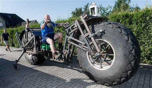 In this photo taken Saturday, Aug. 27, 2016 Frank Dose for the first time rides his self made bicycle in Rade, Germany. With giant tires from an industrial fertilizer spreader and scrap steel, a Dose has built a bike weighing 940 kilograms (2,072 pound) that he plans to pedal into the record books as the world's heaviest rideable bicycle. (Markus Scholz/dpa via AP)
