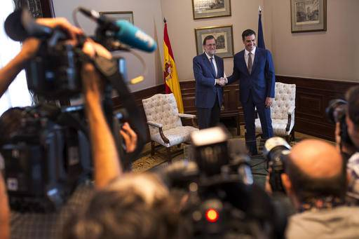 Spain's acting Prime Minister and Popular Party leader Mariano Rajoy, left, shakes hands for the media with Socialists Party leader Pedro Sanchez during their meeting at the Spanish parliament in Madrid, Monday, Aug. 29, 2016. Rajoy is meeting with Sanchez in a last-ditch effort to convince him not to scupper the premier's bid to form a government this week and end the country's eight-month political impasse following two inconclusive elections. (AP Photo/Francisco Seco)