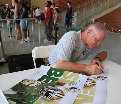 "In this Aug. 6, 2016, photo, acting head coach Jim Grobe autographs a poster during the annual ""Meet the Bear's,"" at McLane Stadium in Waco, Texas. Thousands of Baylor fans received autographs and visited with the 2016 football team. (Rod Aydelotte/Waco Tribune Herald, via AP) /Waco Tribune-Herald via AP)"