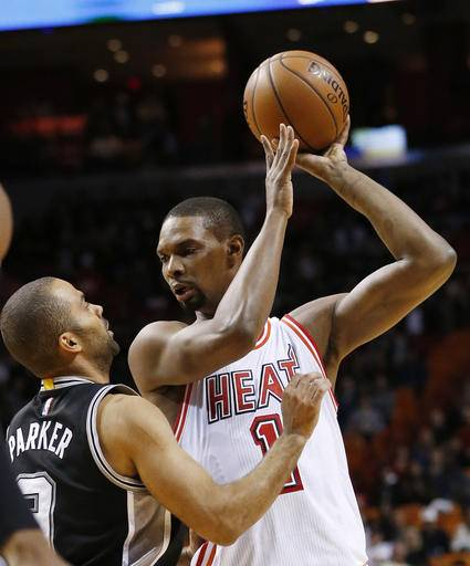 In this Tuesday, Feb. 9, 2016, photo, Miami Heat forward Chris Bosh (1) looks for an opening past San Antonio Spurs guard Tony Parker (9) during the first half of an NBA basketball game in Miami. Bosh released a video Monday, Aug. 29, on Snapchat of him going through a non-contact workout, including some shooting and dribbling, dropping a big hint that he plans to try playing for the Miami Heat again this season.. (AP Photo/Wilfredo Lee)