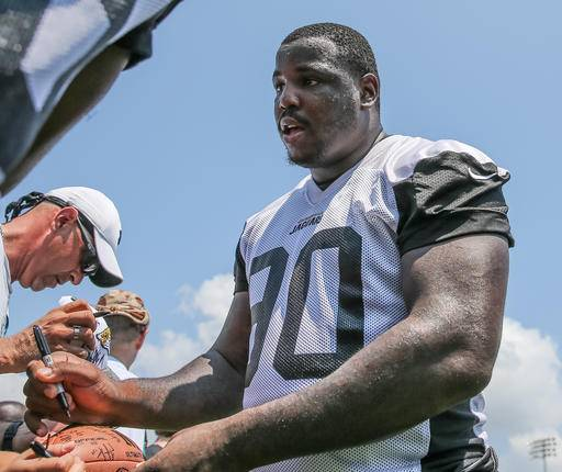 FILE - In this June 14, 2016, file photo, Jacksonville Jaguars defensive tackle Malik Jackson (90) signs a fan's football after an NFL football minicamp practice in Jacksonville, Fla. Owner Shad Khan has been shelling out big bucks for lots of free agents over the past two offseasons like defensive tackle Malik Jackson. (AP Photo/Gary McCullough, File)