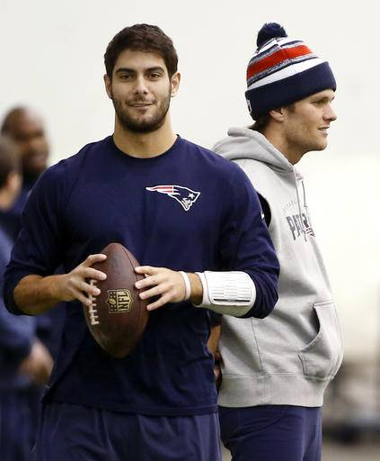 "FILE- In this Jan. 23, 2015, file photo, New England Patriots backup quarterback Jimmy Garoppolo, left, holds a football as starting quarterback Tom Brady, right, stands by during a walkthrough at the NFL football team's facility in Foxborough, Mass. Brady will have to sit out the first four games of this season for his role in the ""Deflategate"" scandal. Garoppolo performs in Brady's absence. (AP Photo/Elise Amendola, File)"