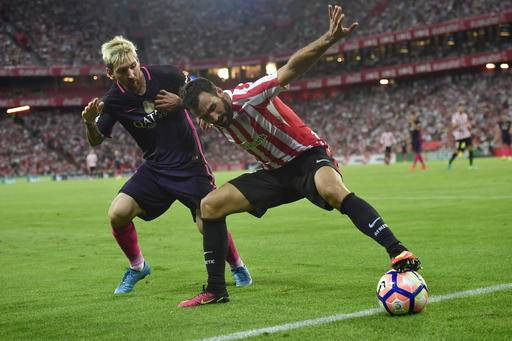 FC Barcelona's Lionel Messi, left, duels for the ball with Athletic Bilbao's Mikel Balenziaga during the Spanish La Liga soccer match between FC Barcelona and Athletic Bilbao, at San Mames stadium, in Bilbao, northern Spain, Sunday, Aug. 28, 2016. FC Barcelona won the math 1-0. (AP Photo/Alvaro Barrientos)
