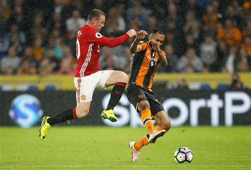 Manchester United's Wayne Rooney, left, and Hull City's Ahmed Elmohamady clash during the Premier League soccer match Hull City versus Manchester United at the KCOM Stadium, Hull, England, Saturday Aug, 27, 2016. (Danny Lawson/PA via AP)