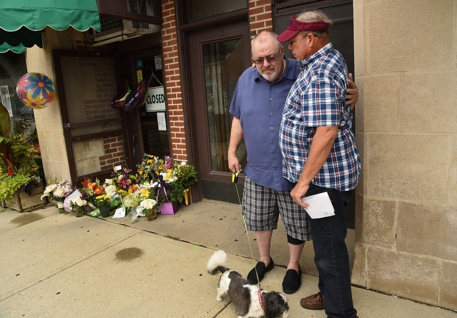 Tim O'Connor is consoled by friend Lee McCloud on Tuesday near a memorial to Roberta Rapata, O'Connor's partner and co-owner of the Catlow Theater and Boloney's Sandwich Shop in Barrington, who died over the weekend.
