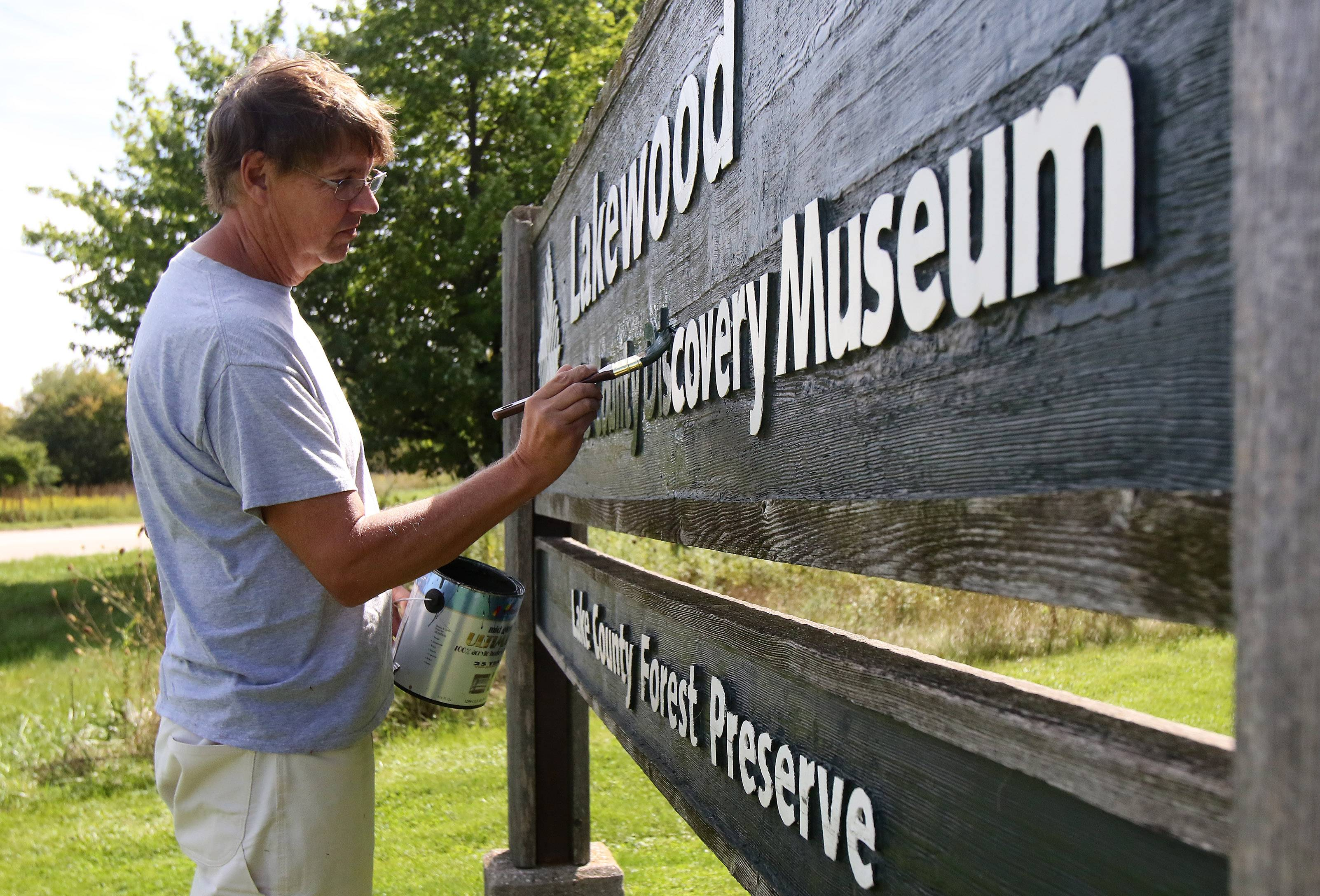 Painter Mike Tylkowski removes the Lake County Discovery Museum's name from the outdoor sign at Lakewood Forest Preserve on the museum's last day of operation, Wednesday. The museum is relocating to the Lake County Forest Preserve District's headquarters building in Libertyville and plans to reopen in late 2017.