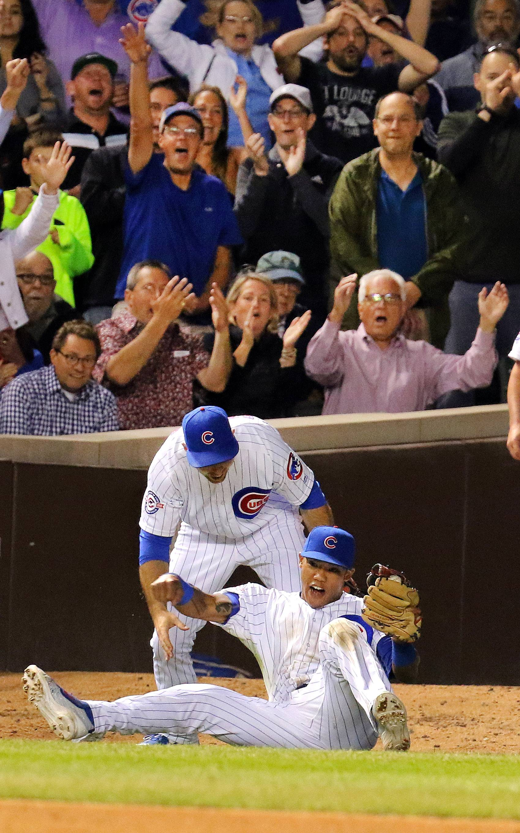 Chicago Cubs shortstop Addison Russell celebrates a catch with Chicago Cubs third baseman Kris Bryant.