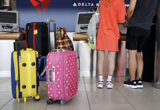 In this July 12, 2016, photo, passengers prepare to check bags at a Delta Air Lines counter at Baltimore-Washington International Thurgood Marshall Airport in Linthicum, Md. Delta Air Lines is rolling out new technology to better track bags throughout its system. (AP Photo/Patrick Semansky)