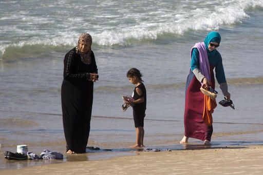 In this Friday, Sept. 2, 2016 photo, Muslim women stand at a beach in Tel Aviv, Israel. France's burkini controversy is boosting the bottom line for Israeli makers of modest swimwear. Israel, home to large populations of conservative Jewish and Muslim women, has cultivated a local industry of modest swimsuits, and the full-body outfits that have caused uproar in France have been a common sight on Israeli beaches for several years.