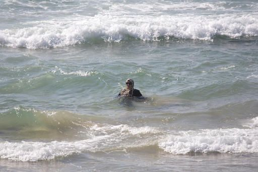 In this Friday, Sept. 2, 2016 photo, Muslim woman bathes in the Mediterranean Sea in Tel Aviv, Israel. France's burkini controversy is boosting the bottom line for Israeli makers of modest swimwear. The country, home to large populations of conservative Jewish and Muslim women, has cultivated a local industry of modest swimsuits, and the full-body outfits that have caused uproar in France have been a common sight on Israeli beaches for several years.