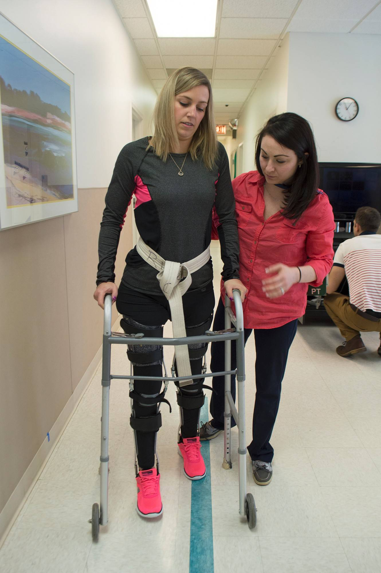 Her knees held rigid by braces, Kelsey Ibach uses a walker for support as she takes steps with the help of therapist Megan Greenwood last year at the Rehabilitation Institute of Chicago. The Arlington Heights native, a passenger in a 2014 car crash that left her paralyzed below the waist, recently earned her scuba diving certification and will go surfing again this winter.