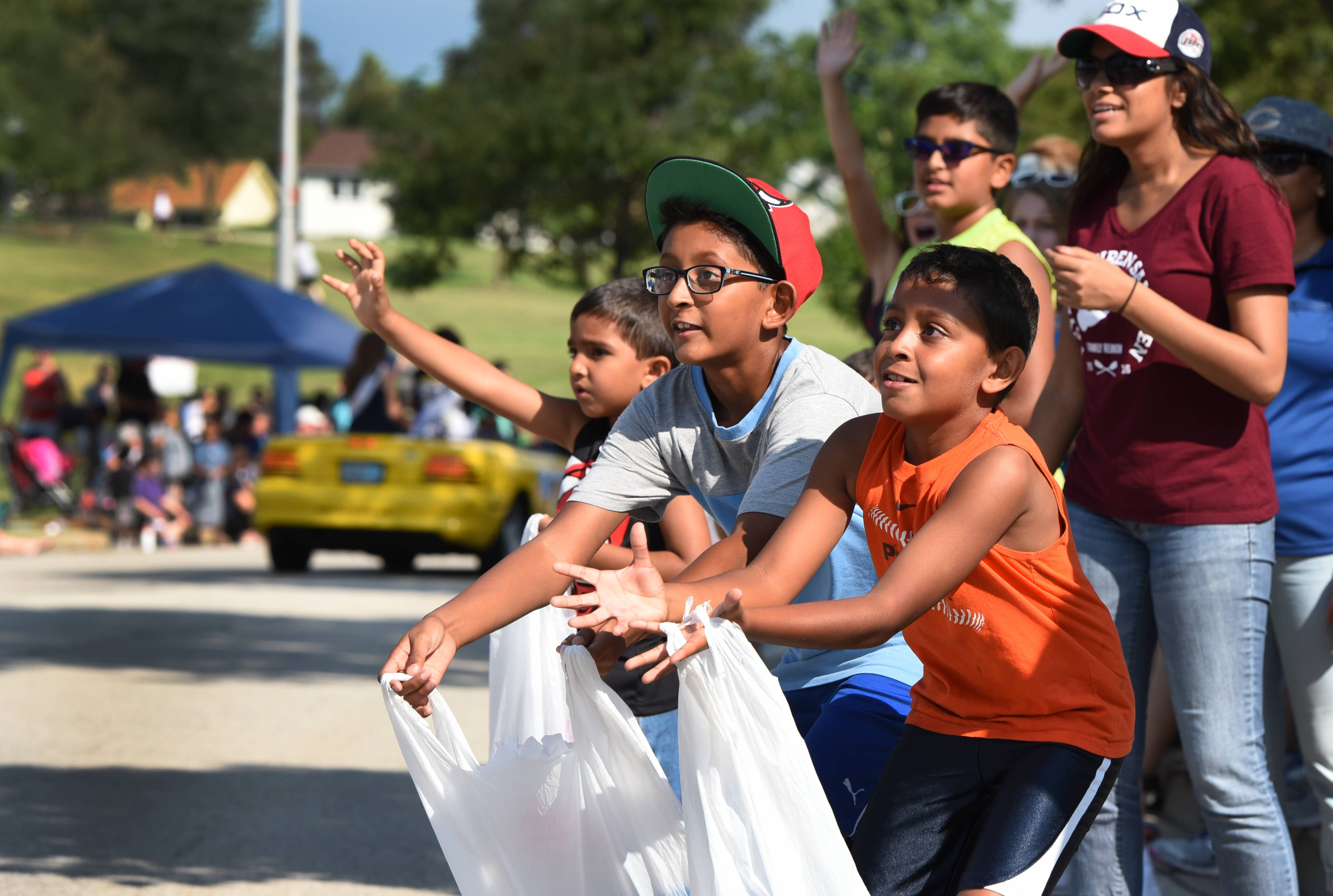 Yup Patel, right, 8 and his brother Veer Patel, 11 of Bartlett position themselves to catch candy during the Schaumburg Septemberfest parade on Monday.