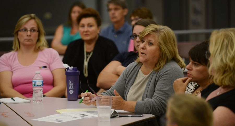 Angela Santoro asks a question during a community meeting held Thursday at Winston Campus Elementary School in Palatine. District 15 wants voter approval to borrow $130 million for the construction of two new schools. The district would close its oldest building.
