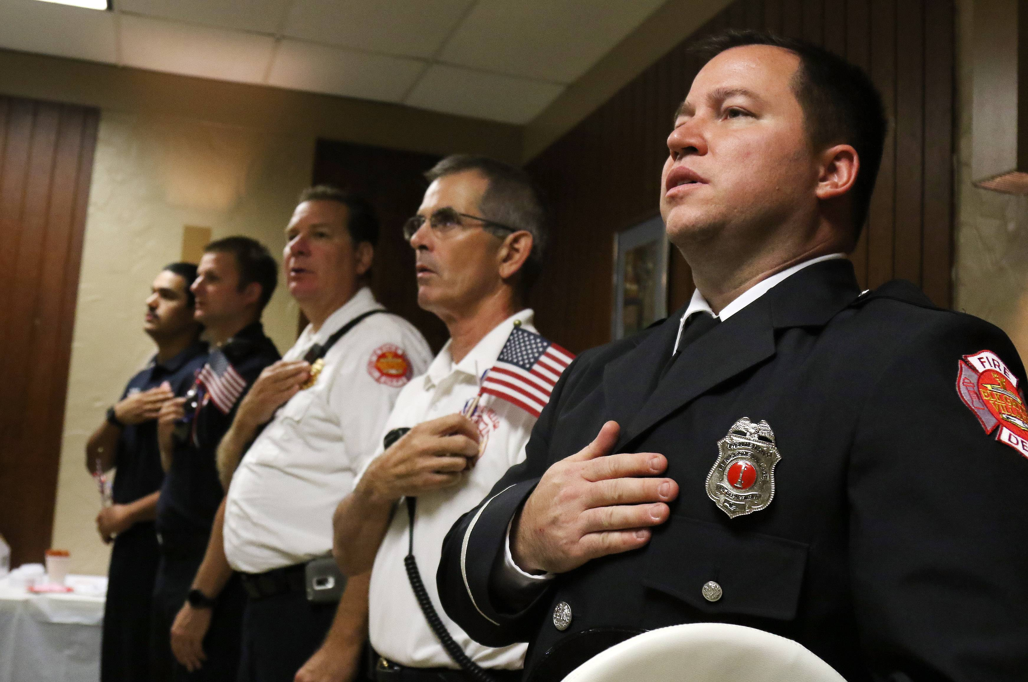 Elk Grove Village Fire Dept. Lt. David Hoppe, right, and Lt. Rick Krieger joins other members of the fire department in the Pledge of Allegiance during the Elk Grove Village September 11, 15th Anniversary Celebration on Sunday at the VFW Post 9248 hall. In addition to the VFW, the Community Character Coalition, the Heart of a Marine Foundation, Shennyo-en Temple and the Elk Grove Interfaith Council sponsored the event.