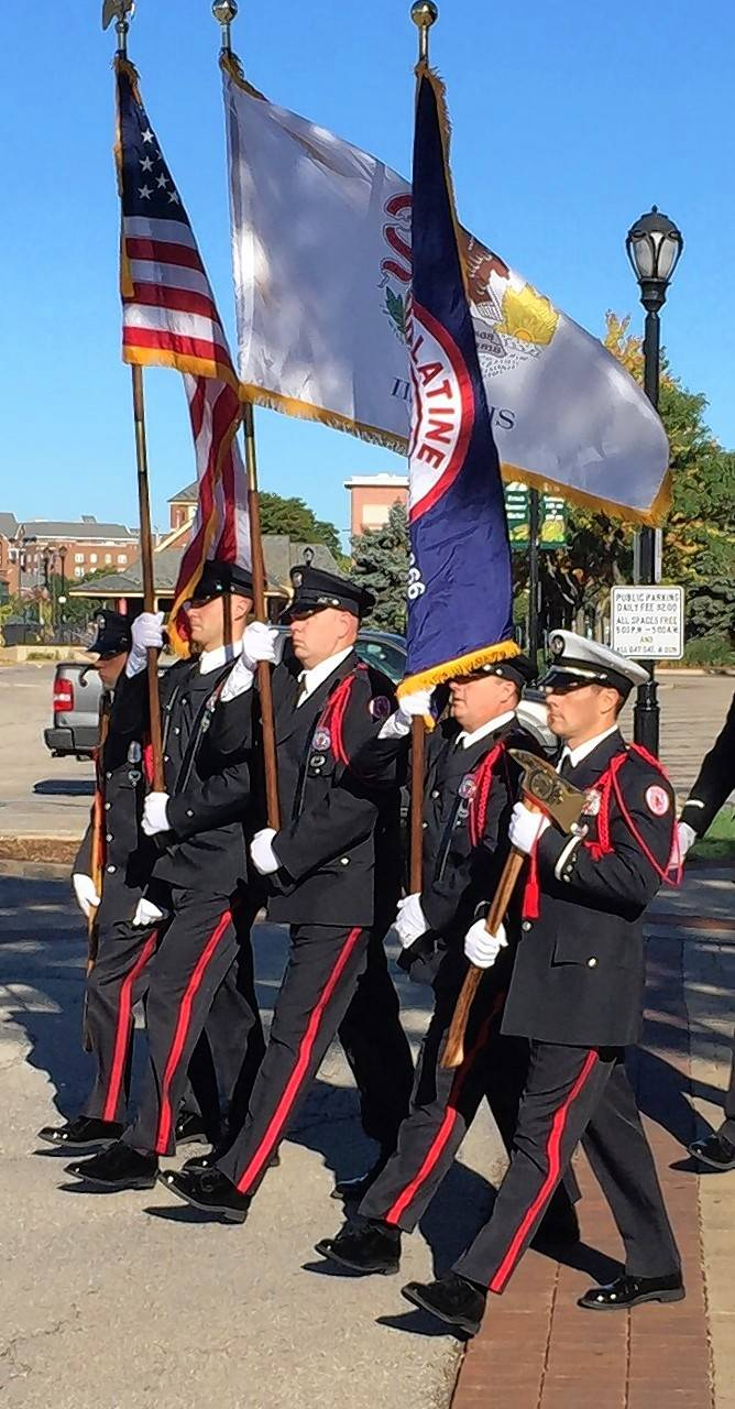 The Palatine Fire Department Honor Guard marches toward the Palatine Firefighters Memorial.