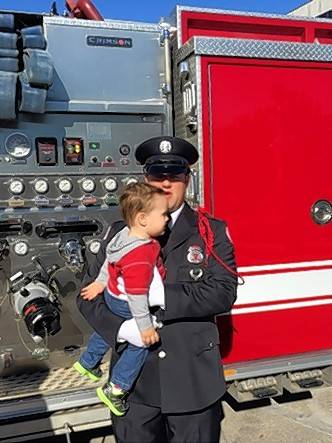 Robert Diamond, a member of the Palatine Fire Department Honor Guard, holds his son, Ryan, following Sunday's Sept. 11 remembrance in Palatine.