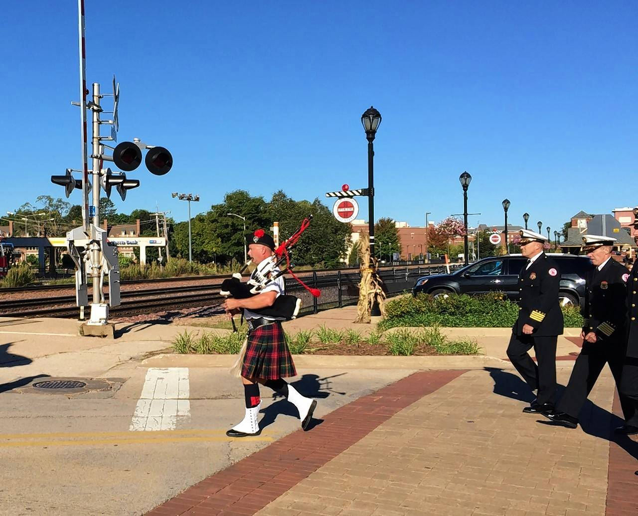 Firefighter Jeb Kaiser, with bagpipes, crosses the tracks on Brockway Street en route to the Palatine Firefighters Memorial.